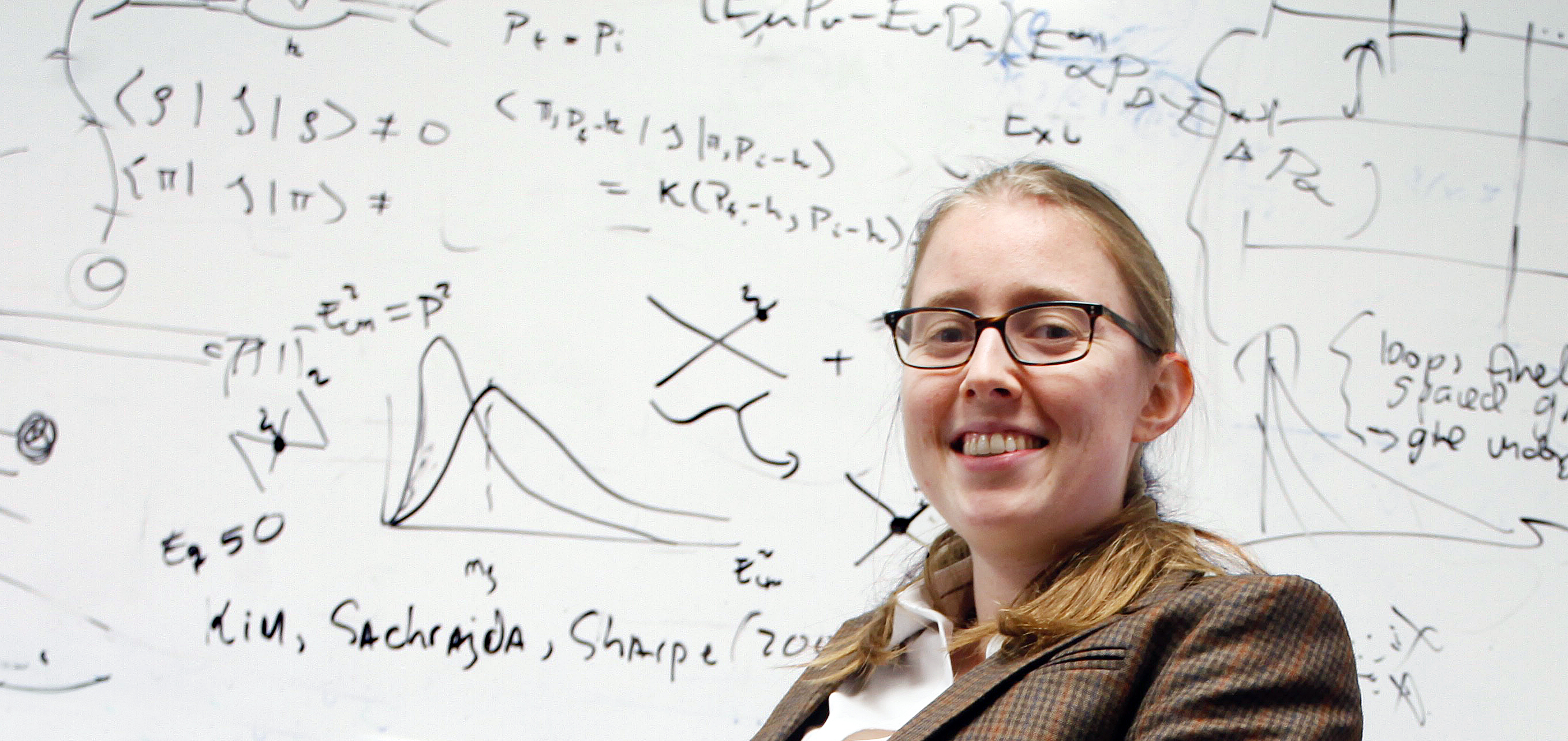Phiala Shanahan seated in front of a white board.