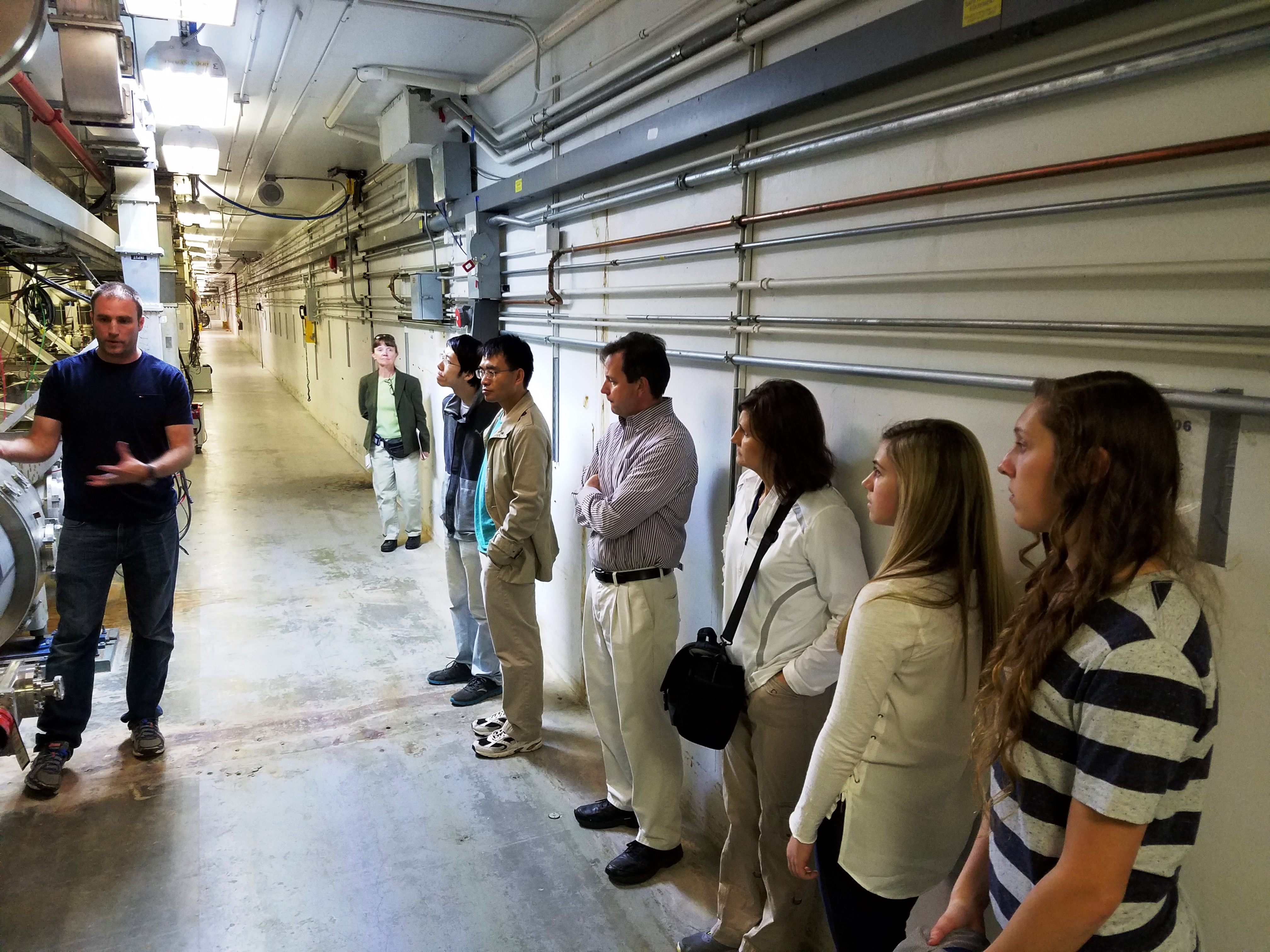 Mike Aiken (left) leads a group of high school students in a tour of the accelerator tunnel, May 2017.