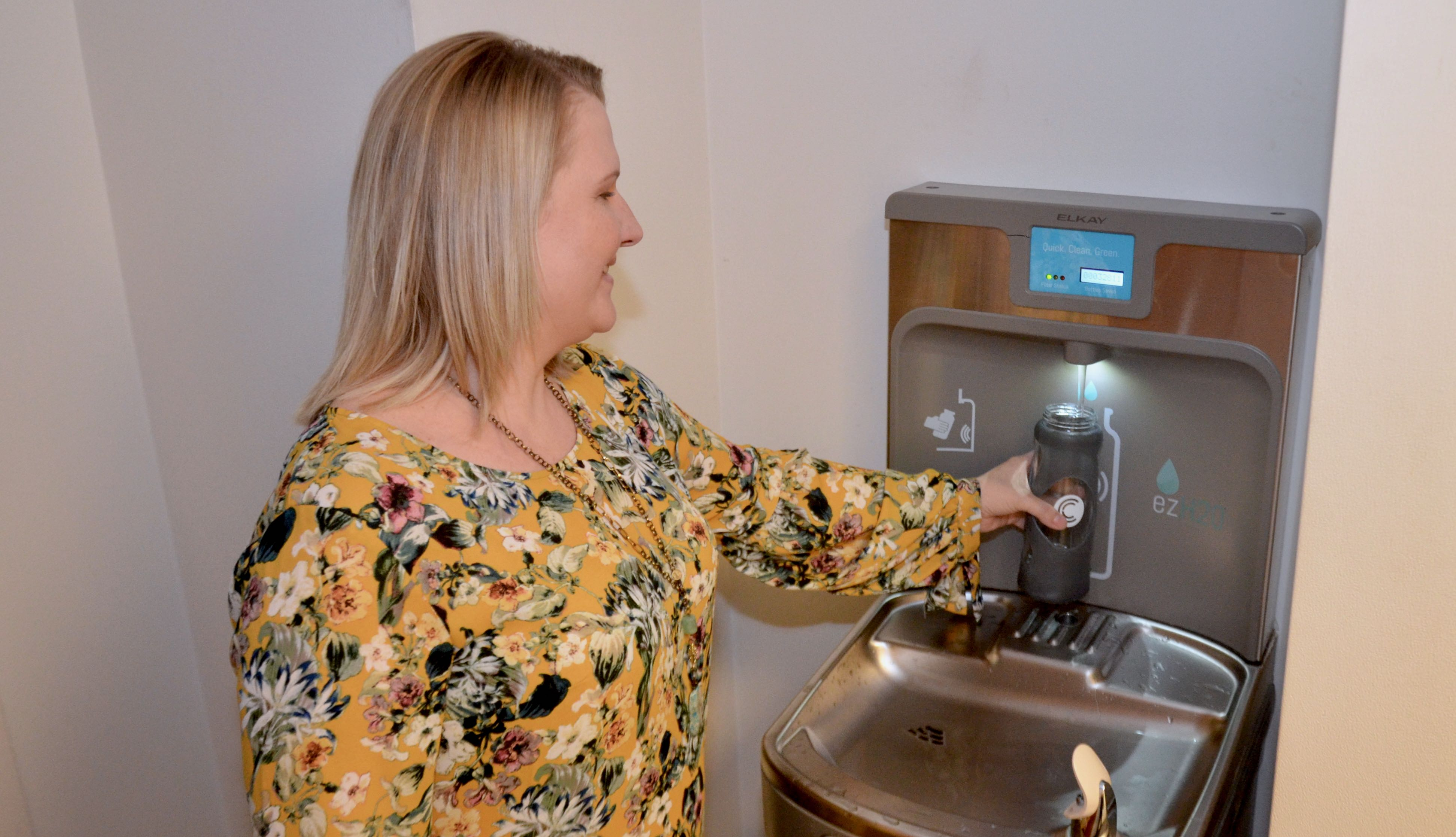 Woman fills a generic water bottle from an Elkay Water Refill stations.