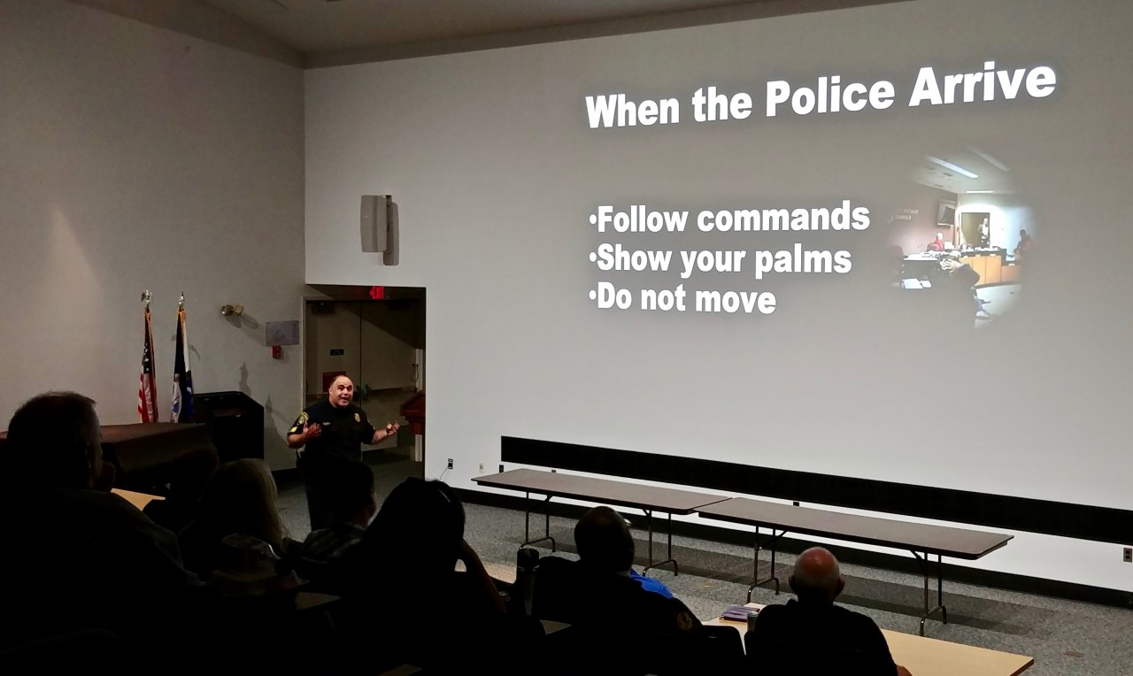 Image taken during presentation shows Sgt. Randy Cupp and slide indicating that when police arrive, you should follow co,,ands, show your palms and do not move unless ordered to do so.
