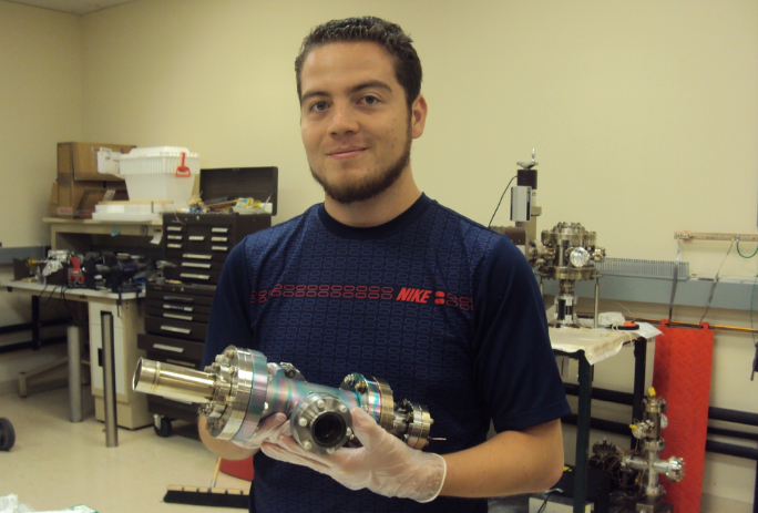 Salvador Sosa implementing vacuum techniques to assemble an ion source at JLab's polarized electron source vacuum lab.