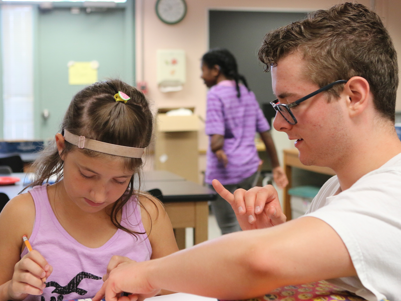 A camp counselor helps a student with an activity at the 2019 Deaf Science Camp