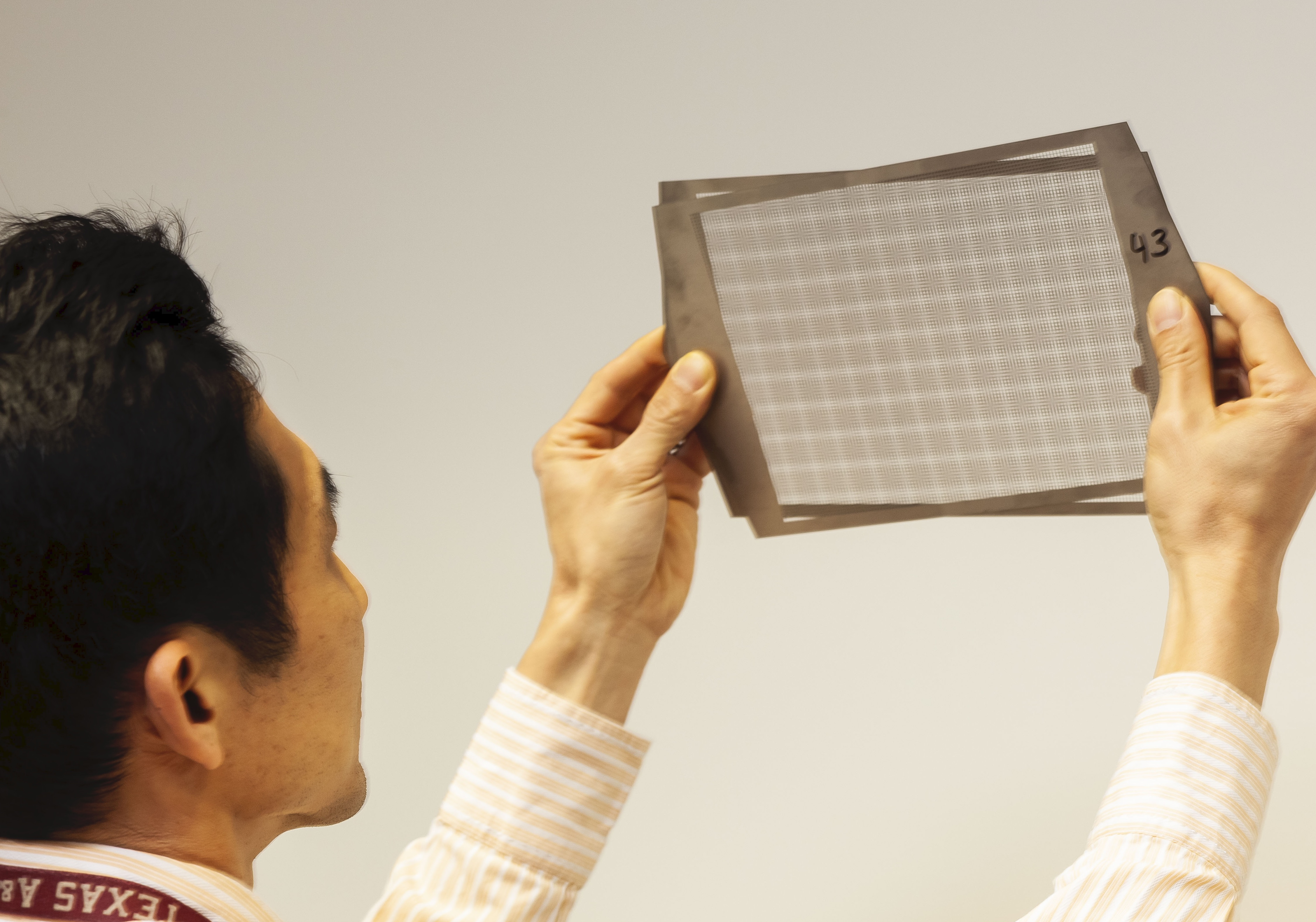 An inventor inspects components of a device that he invented