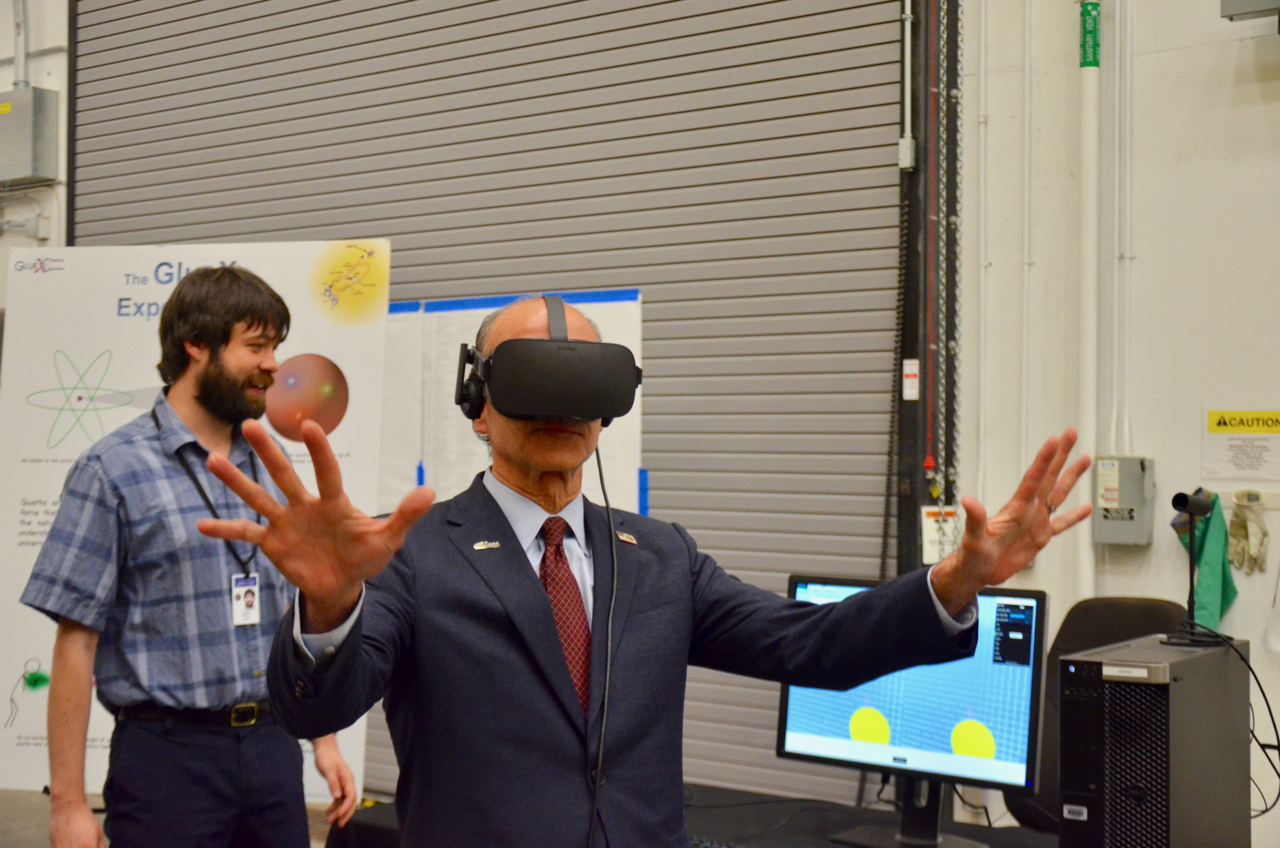 Menezes with virtual reality headset, arms outstretched