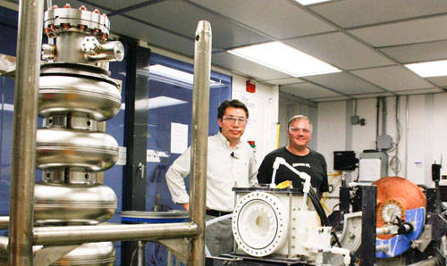 JLab's Rongli Geng and Fermilab's Jim Follkie stop for a photo in the SRF Electro-Polishing Lab. The milestone achieving cavity, AES8, is sitting in the left foreground