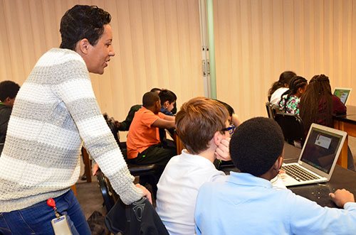 Dana Cochran, Jefferson Lab staff member, helps students as they participate in a coding activity.