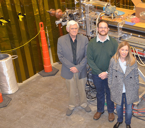 College of William and Mary graduate student Matthew Burton (center left), pauses for a photo in Jefferson Lab's SRF Institute with his Advisor, R. Ale Lukaszew (center right), the W&M Virginia Microelectronics Consortium Distinguished Professor of Physics, and his Jefferson Lab Advisor, Larry Phillips. Behind them is the cavity deposition system Burton is using in his research which is aimed at improving superconducting radiofrequency thin-film capabilities. A Department of Energy Office of Science Graduat