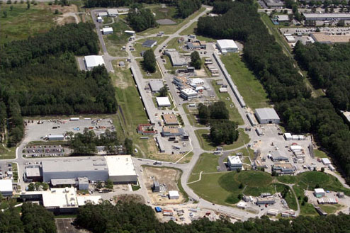 This aerial view of the Continuous Electron Beam Accelerator Facility shows the footprint of the accelerator and the experimental halls where nuclear physics experiments are conducted.The newest experimental facility, dubbed Hall D, which is part of the 12 GeV Upgrade, is visible in the upper left.