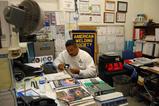 Jenord Alston works at his desk, surrounded by books and papers on welding