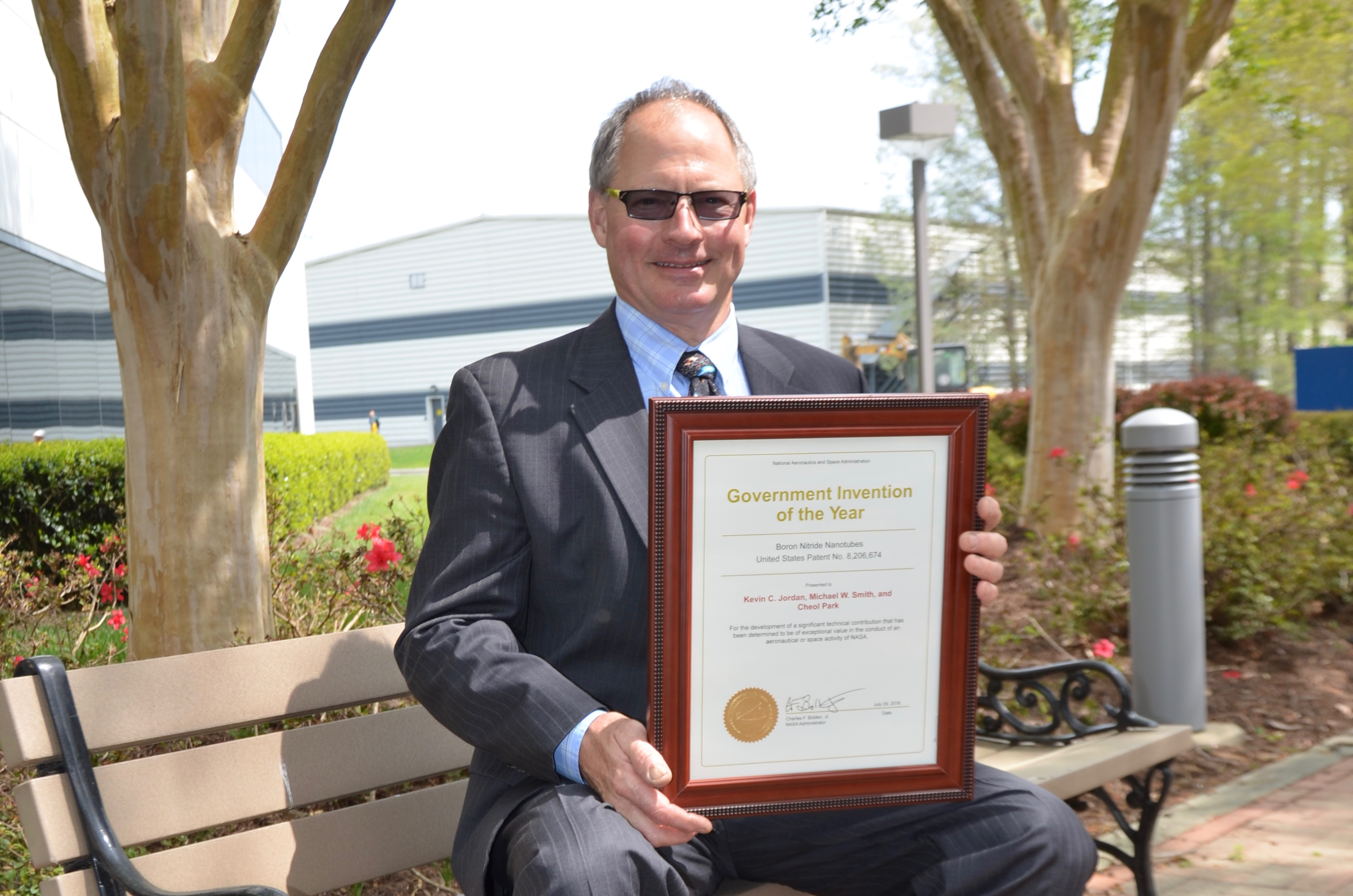 Photo of Kevin Jordan with framed 2016 NASA Invention of the Year award.