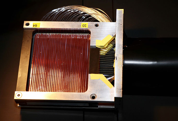 Square detector head with numerous clear glass fibers across the top surface and out the side.