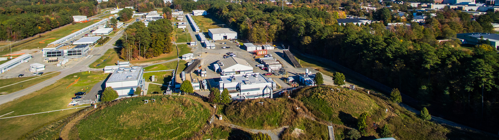Aerial photo of the Continuous Electron Beam Accelerator Facility, showing the above-ground accelerator service buildings, which outline the accelerator's racetrack shape. The three round domes of the Experimental Halls A, B and C are in the foreground, and the Experimental Hall D complex is in the top left corner of the photo.