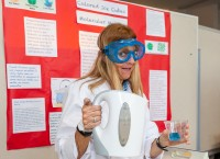A teacher in the JSAT program wears goggles and a lab coat to demonstrate an activity with hot water.