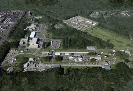 In this aerial view of Jefferson Lab and some of the surrounding area, the accelerator site is visible in the foreground. Experimental Halls A, B and C are visible as the three round mounds on the left, and Hall D and its counting house are on the far right. The long, one-story white buildings sit, respectively, over the North and South Linear Accelerator sections of CEBAF.