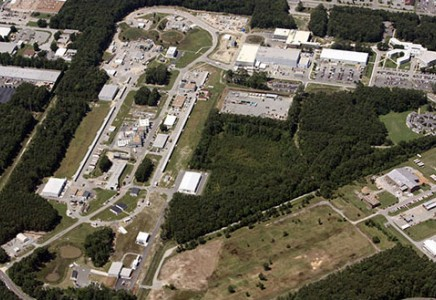 An overhead view of Jefferson Lab showing the racetrack-shaped accelerator and experimental halls to the left