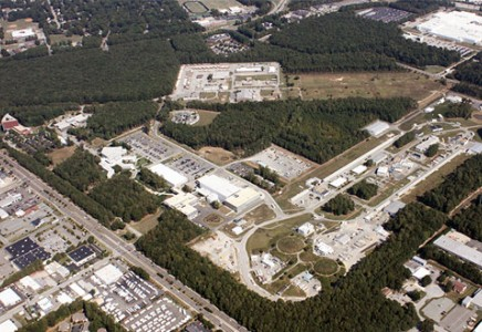 An overhead view of Jefferson Lab. To the right is the racetrack outline of the lab's  accelerator, while at the bottom right the lab's experimental halls are visible as three round mounds. The two white buildings (center) are part of the TEDF. The white building to the left is the EEL building.