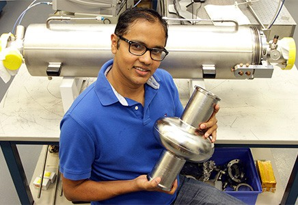 Pashupati Dhakal holding part of a cryomodule