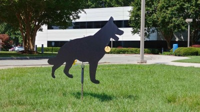 Black corrugated plastic dog cutout attached to a stake embedded in the front lawn of the CEBAF Center Bldg. on the Jefferson Lab campus.