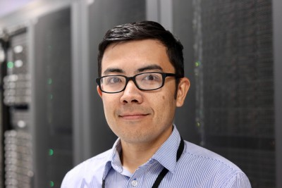 Nobuo Sato stands in front of a supercomputer in Jefferson Lab's Data Center