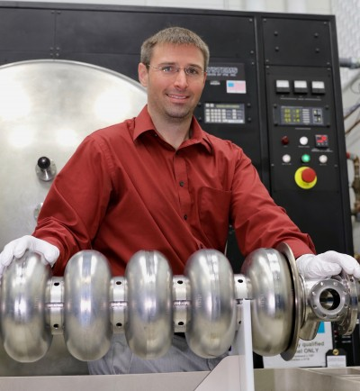 Ari Palczewski shows a superconducting radiofrequency accelerator component